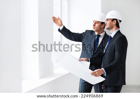 Two men in suits indoors - stock photo