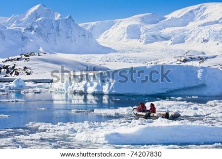 two men in the boat in Antarctica - stock photo