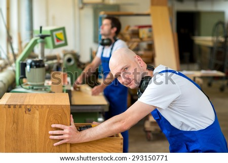 two men in workwear in a carpenter's workshop - stock photo