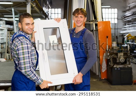 Two men  inspecting  windows production at modern plant