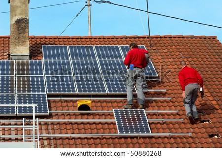 two men installing solar panels - stock photo