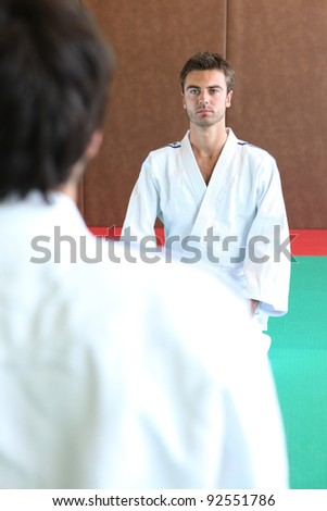 Two men kneeling on a judo mat - stock photo
