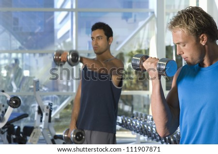 Two men lifting weights at a gym - stock photo