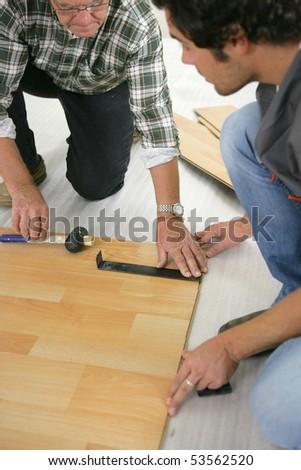 Two men measuring parquet - stock photo