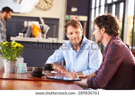 Two men meeting at a coffee shop - stock photo