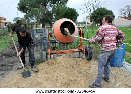 Two men mixing cement - stock photo
