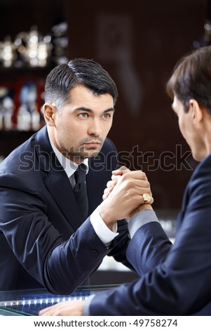 Two men of average years in suits have crossed hands - stock photo