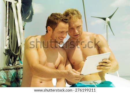 Two men on a sail boat looking at the screen of a tablet computer. - stock photo