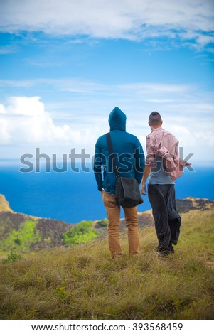 two men on the edge of the Rano Kau volcano, Easter island, Chile, South America - stock photo