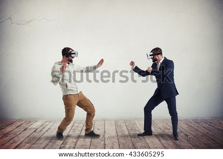 Two men, one in casual clothes, another in dark business suit, are wearing virtual reality glasses and combating in virtual reality in white room with wooden floor - stock photo