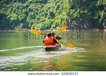 Two men paddle a kayak on the sea. Kayaking in Ha Long Bay - stock photo