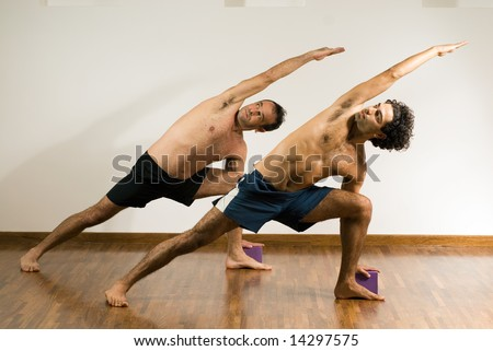 Two men performing a stretch, on hardwood floor. - horizontally framed - stock photo