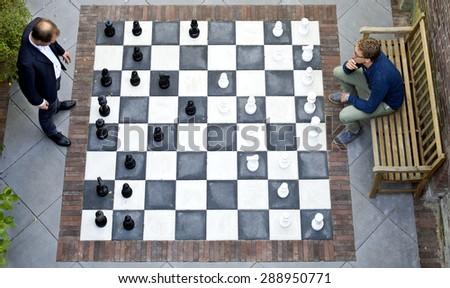 Two men playing a game of outdoor chess with large pieces, seen from above - stock photo