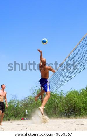 Two men playing beach volleyball - balding man jumps high to catch ball. Shot near Dnieper river, Ukraine. - stock photo