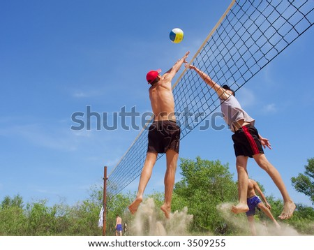 Two men playing beach volleyball - teen in the red hat misses ball from tall guy. Shot near Dnieper river, Ukraine.