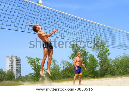 Two men playing beach volleyball - teenager jumps to spike with splash of sand. Shot near Dnieper river, Ukraine.