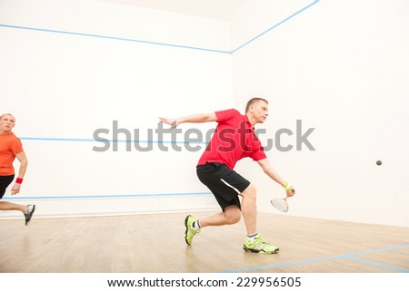 Two men playing match of squash. Squash players in action on squash court