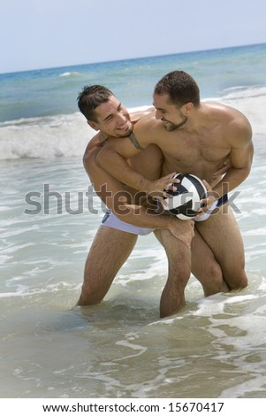 Two men playing volleyball at the beach - stock photo
