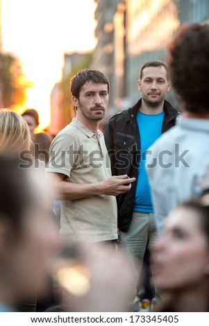 Two men posing on a crowded street in sunset - stock photo