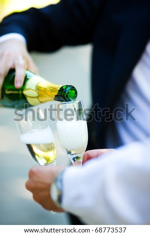 Two men pouring Champagne outdoors hands closeup - stock photo
