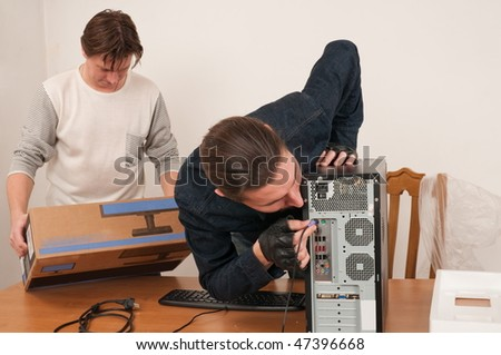 Two men prepare the new computer for connection.