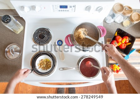 Two men preparing healthy brown wholewheat spaghetti cooking together at the hob as a team stirring the boiling pasta and sauce, overhead view of their hands and ingredients - stock photo