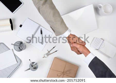 Two men reaching over a desk to shake hands. Shot from a high angle the desk is white as are most of the office items except for a brown wrapped package.  - stock photo