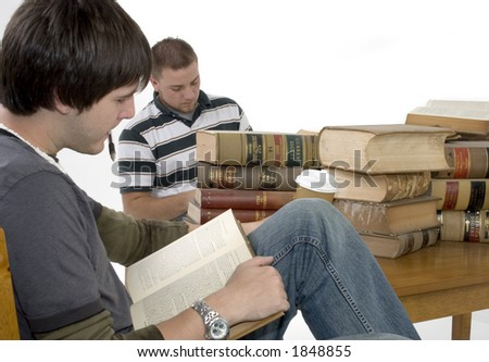 Two men reading through a stack of law books.  Books 70 years old.