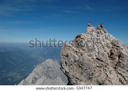 Two men resting and enjoying the view from the top of a mountain peak they have climbeed - stock photo