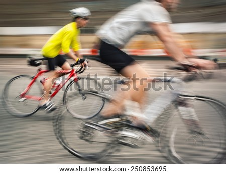 Two men ride bicycles on the streets of the big city. Intentional motion blur and color shift - stock photo