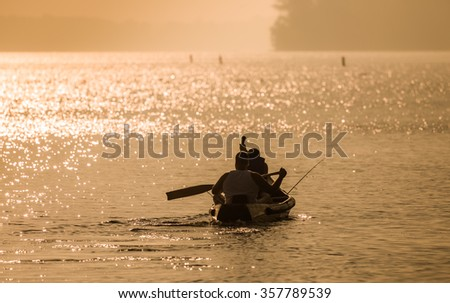 Two men riding small boat in a Provincial Park at Ontario Canada during sunrise - stock photo