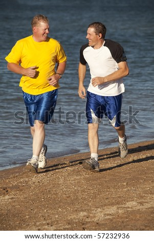 Two men running and laughing on the beach.