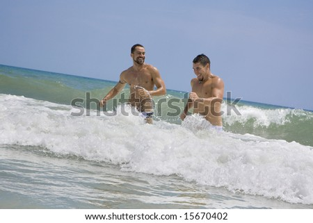Two men running in the ocean - stock photo