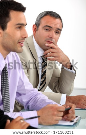 Two men sat on interview panel - stock photo