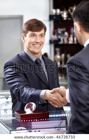 Two men shake each other hands indoor - stock photo
