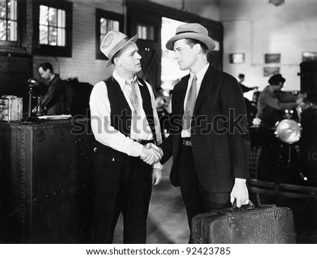 Two men shaking hands in a car shop - stock photo