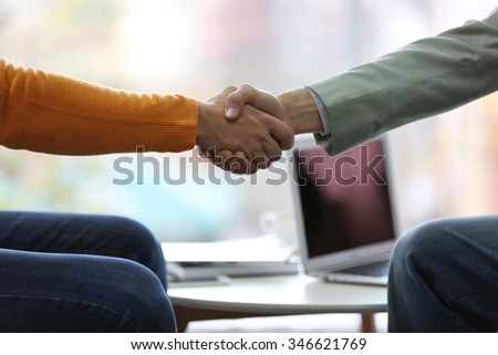 Two men shaking hands in cafe - stock photo