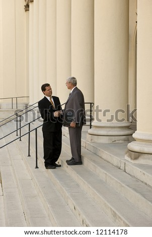 Two men shaking hands on courthouse steps - stock photo