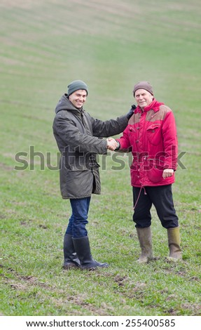 Two men shaking hands on farmland in winter time