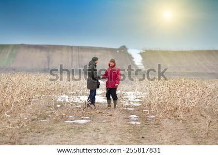 Two men shaking hands on farmland in winter time - stock photo