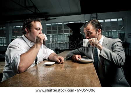 two men share some coffee and look at each other while drinking - stock photo