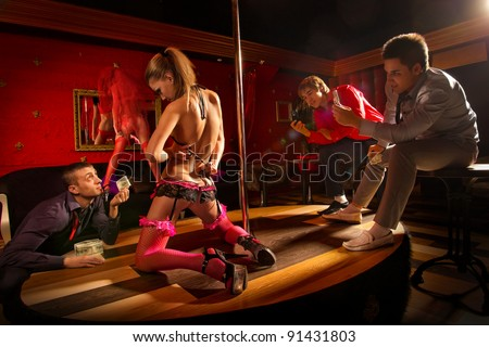 Two men shutting on mobile camera dancing woman and another one offering money to a stripper - stock photo