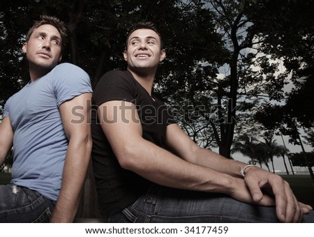 Two men sitting and glancing over shoulder - stock photo
