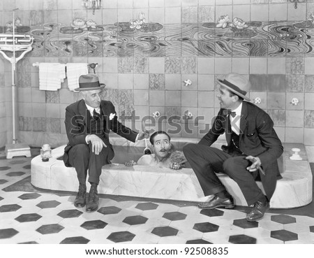 Two men sitting at the edge of a bathtub in suits and scrubbing a friends back - stock photo
