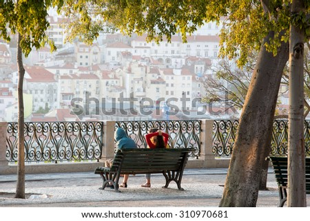 Two men sitting on a bench and  watching sunrise in Lisbon, capital of Portugal, in the very early morning after a festival during night - stock photo