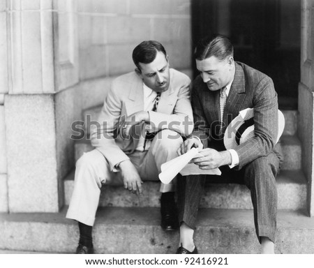 Two men sitting on steps and reading a document - stock photo