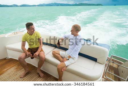 Two men sitting , talking and drinking beer on the yacht