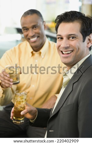 Two men smiling with drinks - stock photo
