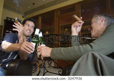 Two men smoke cigars - stock photo