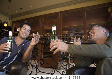 Two men smoking cigars and drinking beer - stock photo